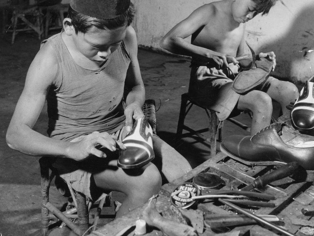 Dalam foto, nampak dua bocah sedang menyemir sepatu di sebuah toko pada tahun 1955. Horace Bristol/Getty Images.