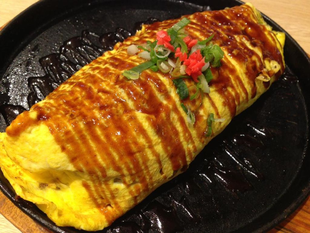 Omelet Yakisoba tersaji dalam hot plate. Omelet ukuran besar diberi topping saus cokelat mirip untuk okonomiyaki, taburan beni shoga kemerahan dan daun bawang.