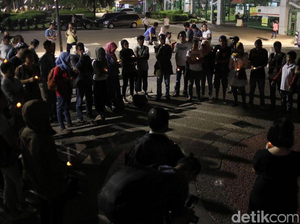 Para aktivis berdiri membentuk lingkaran sambil menyalakanlampu.