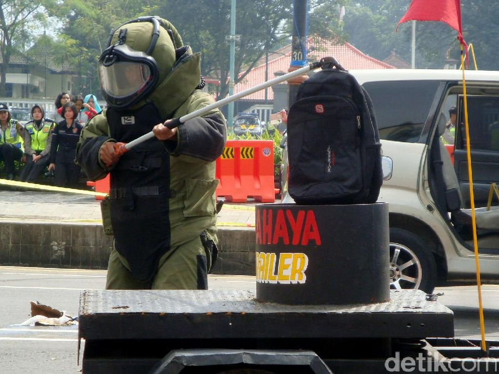 Dalam simulasi, polisi berpakaian anti bom nampak mengamankan sebuah tas mencurigakan yang diduga berisi bom.