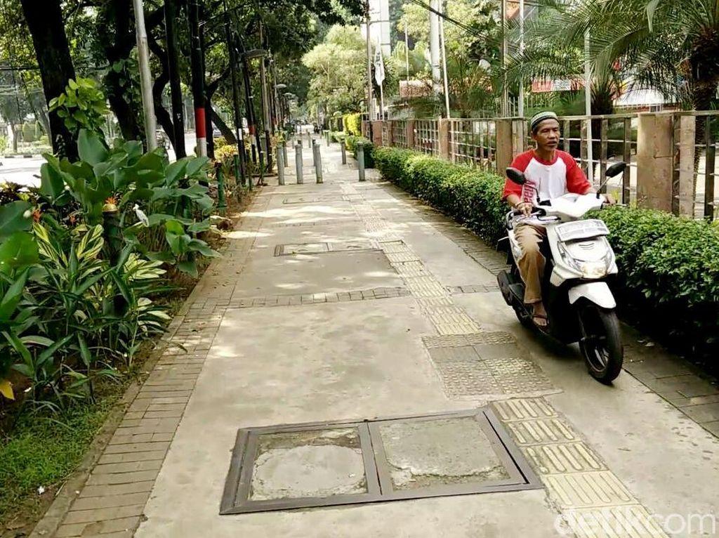 Seorang pemotor terlihat menggunakan jalur pejalan kaki (trotoar) di kawasan menteng, Jakarta Pusat, Minggu (16/7/2017).