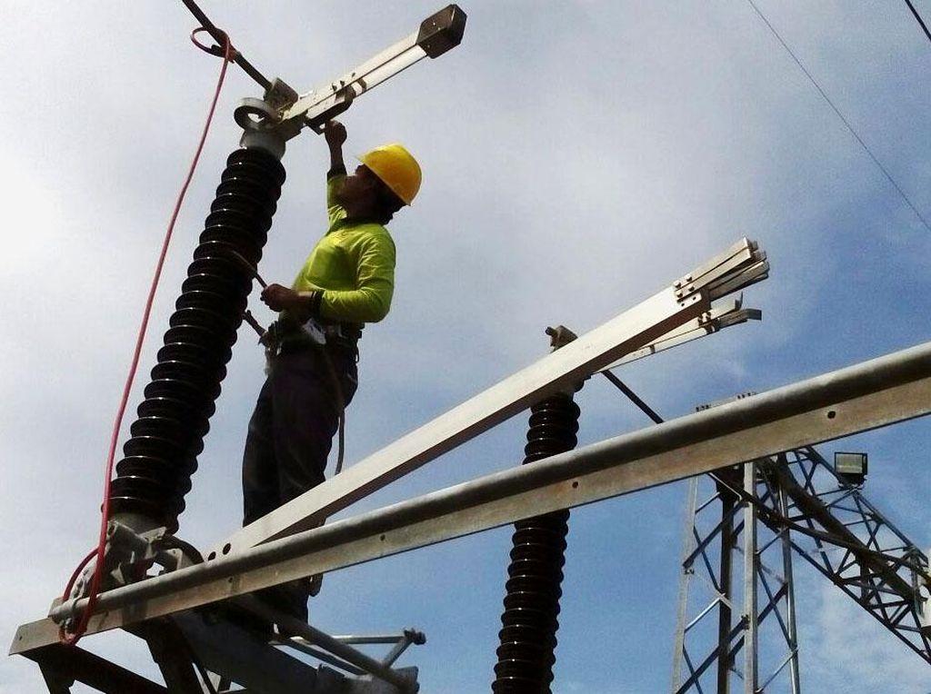 Seorang petugas PLN memanjat tower untuk memasang jaringan listrik. Pool/PLN.