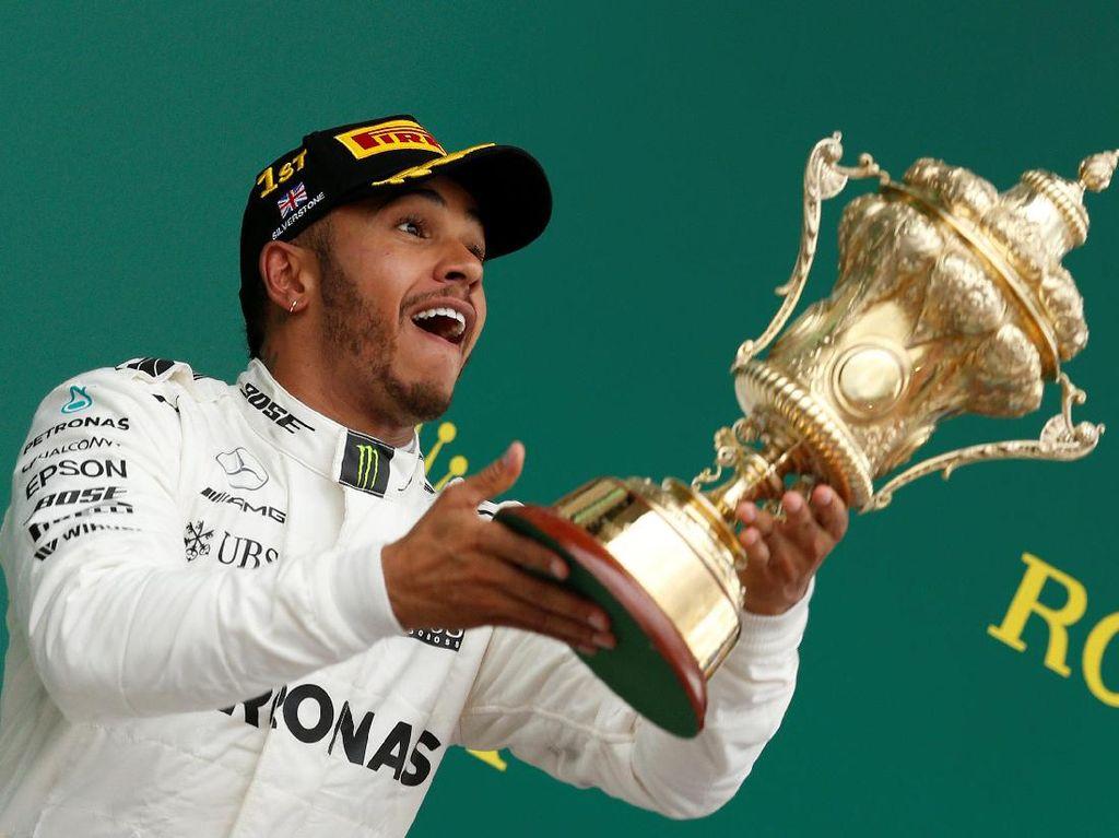 Masih larut dalam kegembiraan di atas podium, Hamilton pun sempat melempar-lemparkan pialanya -- yang tentu saja ia tangkap lagi. (Foto: REUTERS/Andrew Boyers)