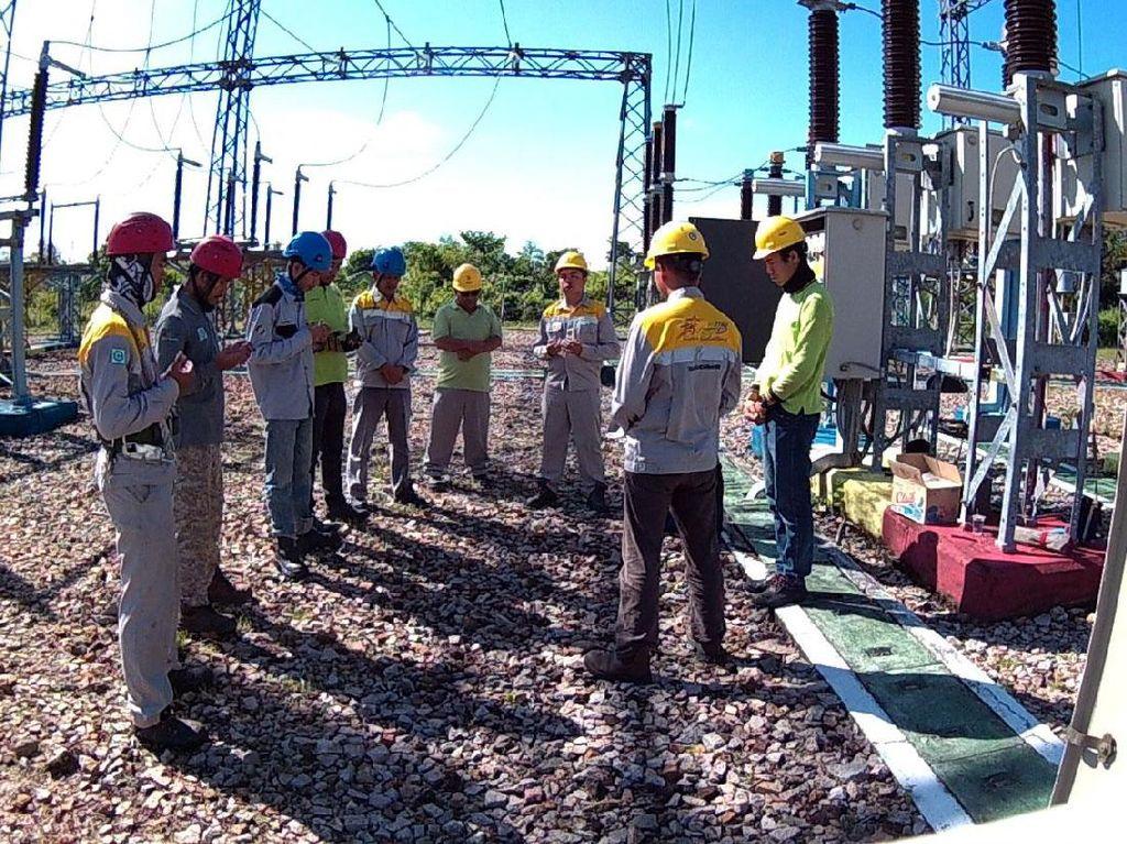 Para petugas PLN doa bersama sebelum bekerja mengecek jaringan listrik. Pool/PLN.