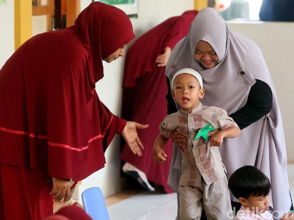 Seorang ibu mengantar anaknya ke dalam kelas.