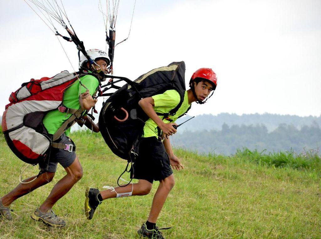 Aris Pribaya (kiri) dan putranya, Pangeran Dirgantara (Jawa Barat) sedang lepas landas dalam nomor Terbang Tandem, Seri III Kejuaraan Ketepatan Mendarat Paralayang TROI (Trip Of Indonesia) IV 2017. Humas FASI/Tagor Siagian.