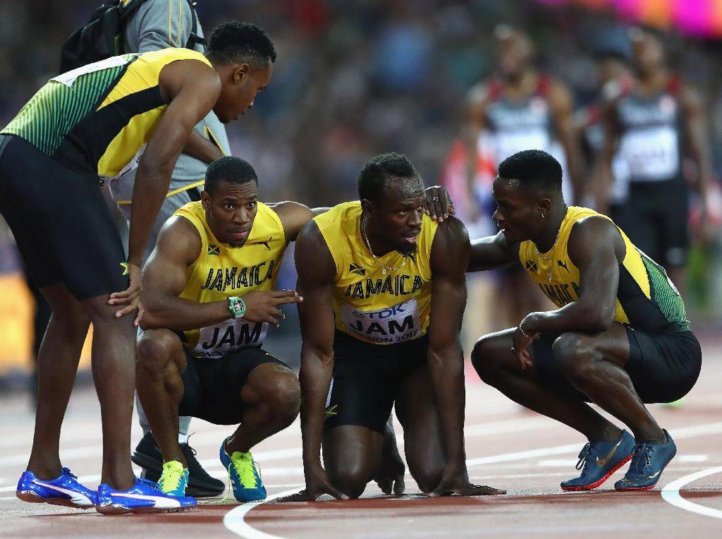 Bolt tak mau dibantu kursi roda. Dia meninggalkan lapangan dengan dibantu oleh rekan satu timnya.(Michael Steele/Getty Images)