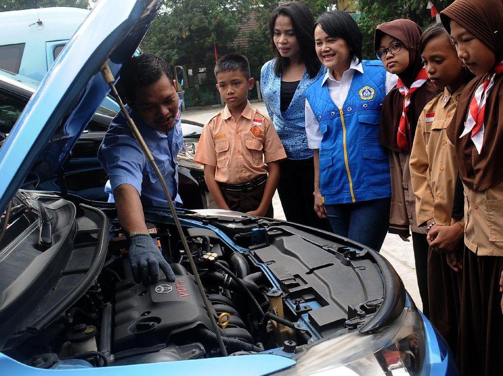 Direktur Marketing PT. Blue Bird TBK Amelia Nasution (tiga kiri) dan Yasinta Widowati Sekretaris Pengurus Yayasan Gerakan Nasional Orang Tua Asuh (GNOTA) bersama anak-anak murid SDN 03 Pondok Pucung Tangerang Selatan mendengarkan penjelasan kru mekanik Blue Bird. Pool/dok. Blue Bird.