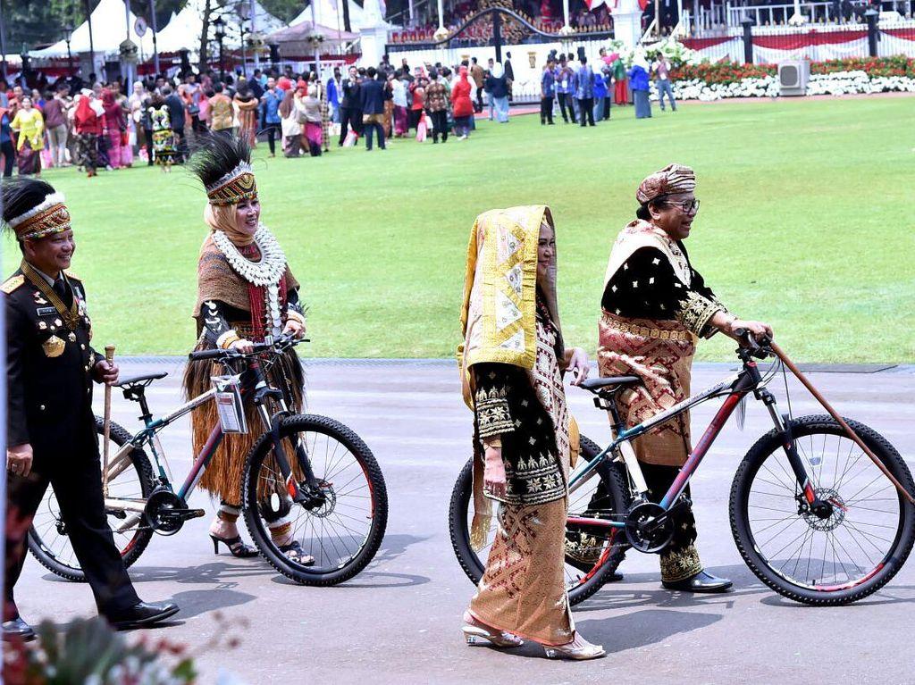 Istri Kapolri dan Ketua DPD Oesman Sapta Odang menuntun sepeda hadiah. Foto: Biro Pers Setpres