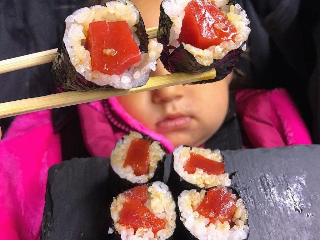 Sepertinya ini sedang berada di restoran sushi. Dua buah sushi dengan isian tuna diapit dengan kedua sumpit. Loh, terlihat seperti menggunakan kacamata ya.Foto: Instagram: FoodBabyNy