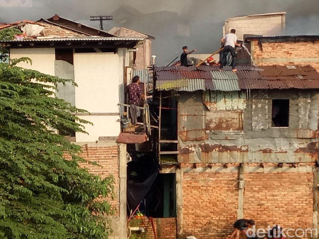 Angin kencang, asap ke mana-mana. Karena lokasi kebakaran berada di gang sempit, petugas pemadam kebakaran melewati atap-atap rumah itu untuk mencapai titik pemadaman. / Foto: Muhammad Fida Ul Haq/detikcom