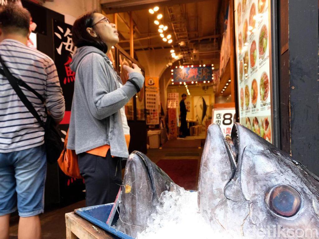 Pengujung melihat-lihat menu di salah satu restoran di Tsukiji Fish Market.