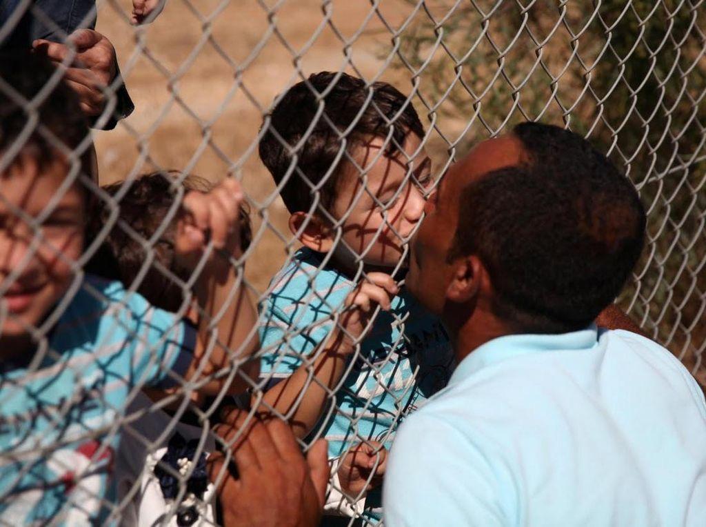 Anak-anak Ammar Hammasho juga berlarian dan semangat menciumi sang ayah. Anak kedua Ammar Hammasho sendiri tewas akibat serangan udara di Suriah (Foto: REUTERS/Yiannis Kourtoglou)