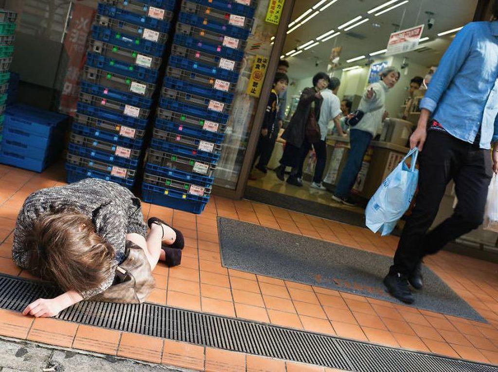 Kasihan, wanita ini sampai tertidur di depan supermarket. Karena Jepang termasuk negara aman, tas bermereknya tidak diambil orang. Foto: Lee Chapman