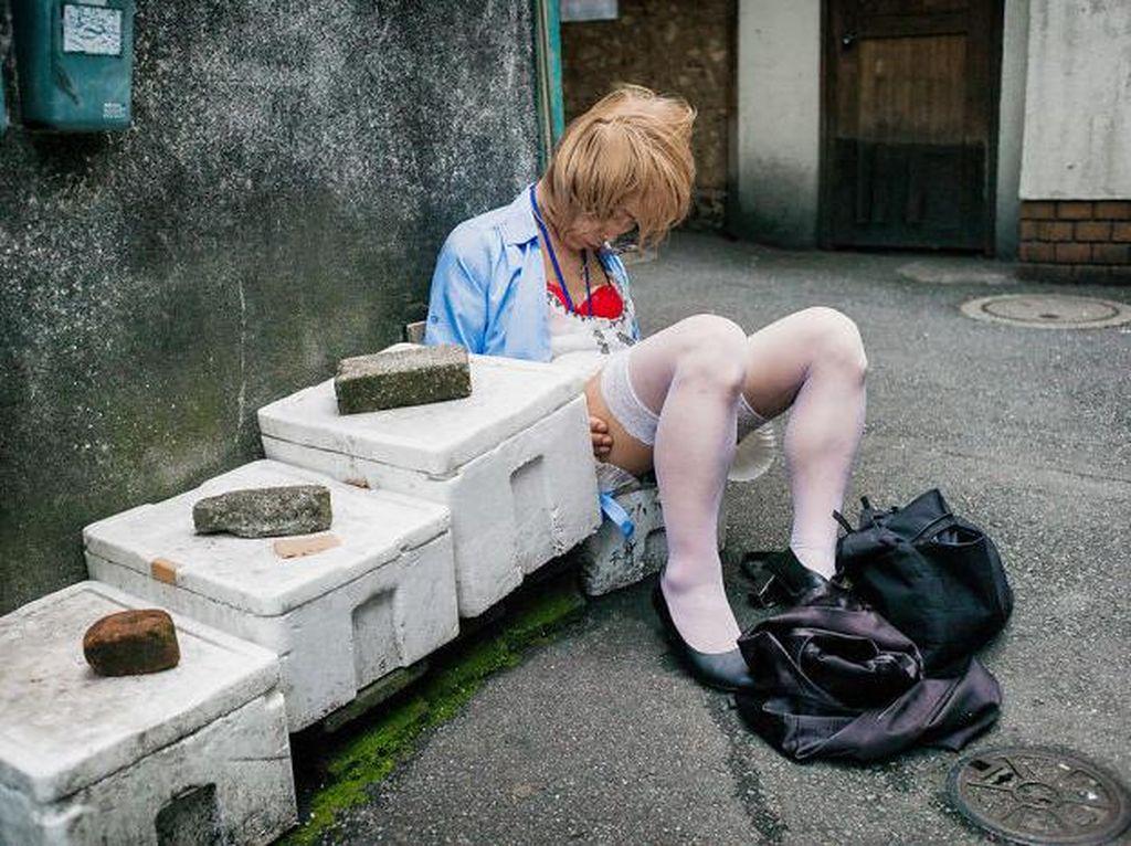 Fotografer Inggris, Lee Chapman, mendokumentasikan sisi lain dari warga Jepang. Ia memotret orang mabuk yang tak sadarkan diri di area publik. Seperti wanita di samping deretan kotak ini. Foto: Lee Chapman