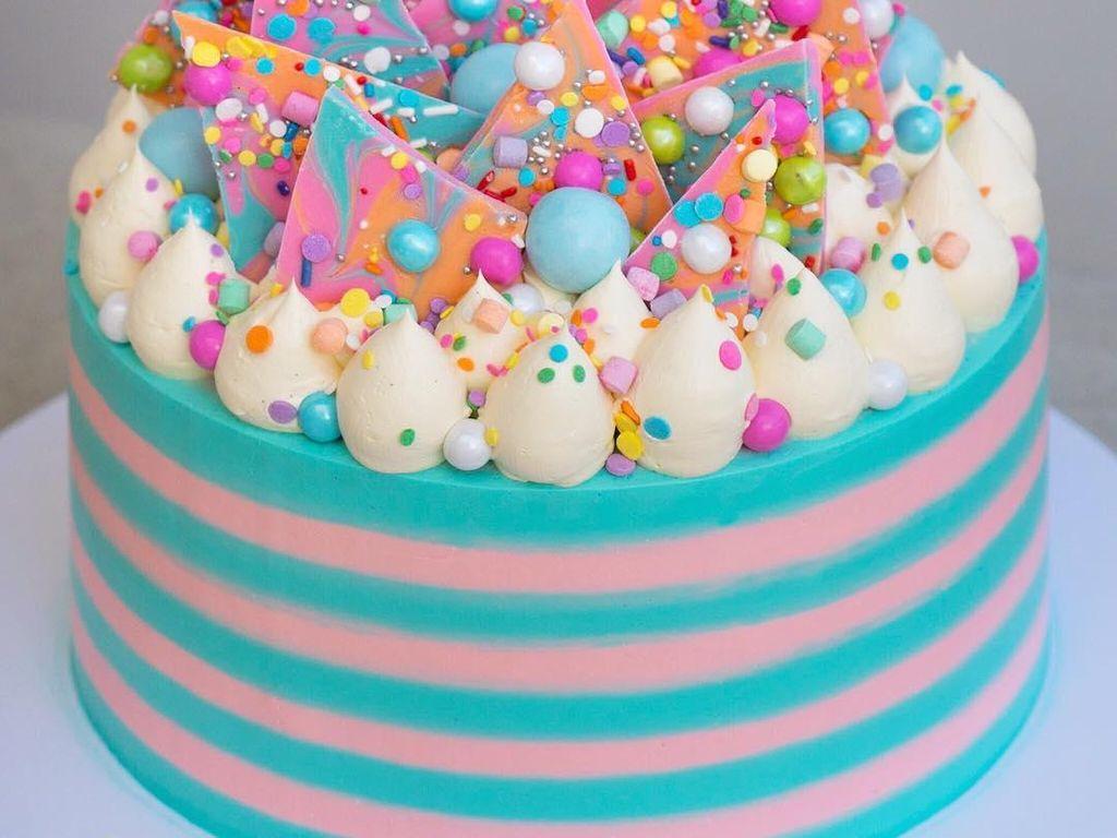 Cake cantik ini berupa vanilla cake dengan isian selai kacang dan potongan karamel. Dekorasinya memakai Swiss meringue buttercream dan cokelat pelangi unicorn. Lucu banget ya? Foto: Katherine Sabbath