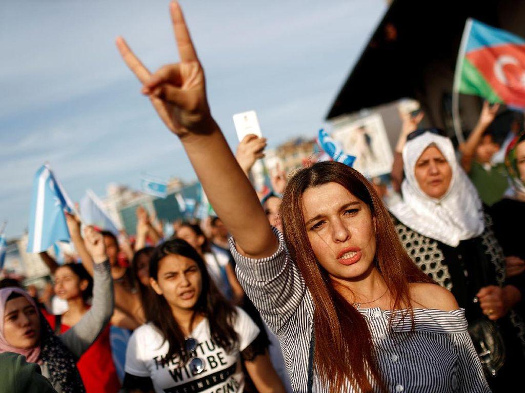 Orang-orang Turki berdemonstrasi menentang referendum Kurdi itu. Terlihat perempuan mengacungkan gestur serigala abu-abu Turki yang ultra-nasionalistik. Mereka berdemo di Istanbul Turki, 24 September 2017. (Murad Sezer/REUTERS)