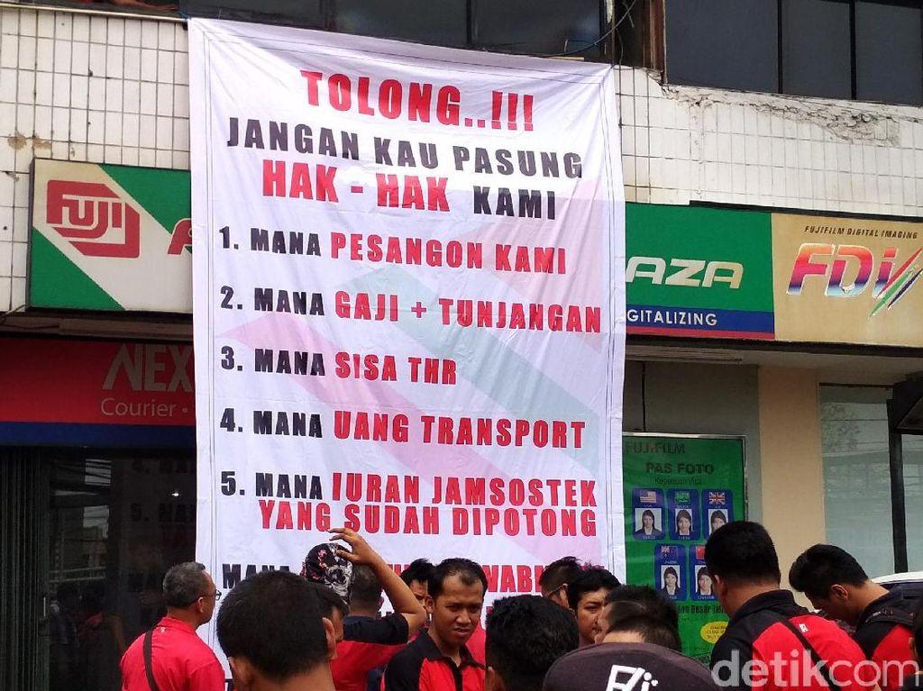 Mantan pegawai 7-Eleven memasang spanduk tuntutan di depan PT Modern Internasional Tbk (MDRN) selaku induk usaha dari PT Modern Sevel Indonesia (MSI).