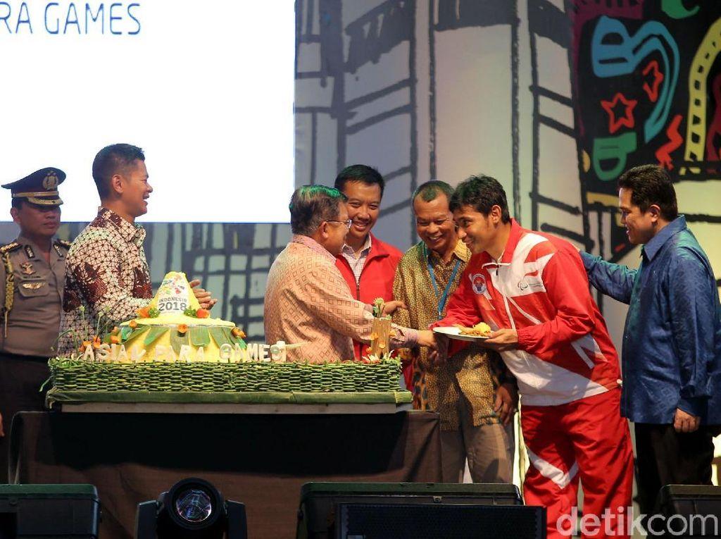 Wapres JK menyerahkan potongan tumpeng kepada peraih medali emas Asian Para games ke-IX di Malaysia.