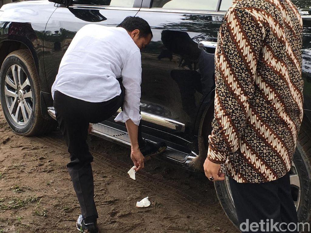 Kaki kanannya diangkat dan ditempatkan ke pijakan mobil. Sambil menunduk, tisu yang dipegangnya disapukan ke sepatu pantofel berwarna hitam tersebut. Foto: Jordan/detikcom