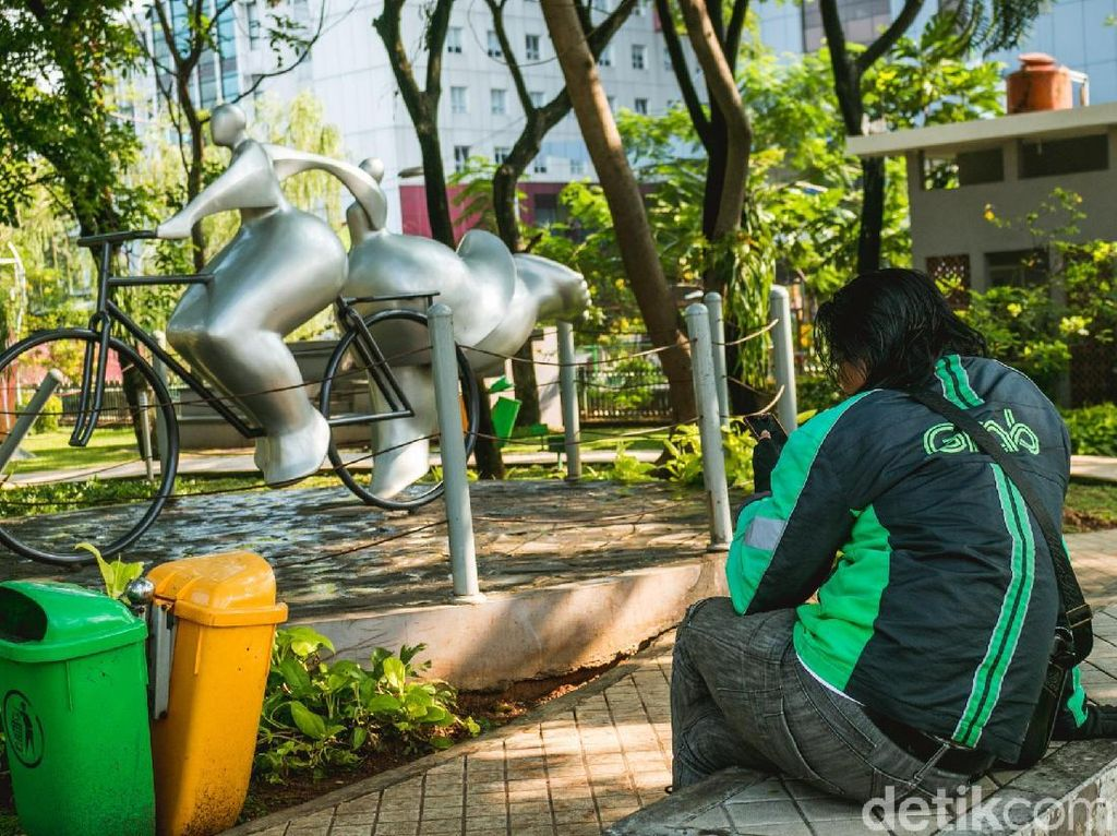 Seorang pengendara ojek online duduk menikmati keindahan Taman Potret sembari menunggu panggilan dari pelanggannya.