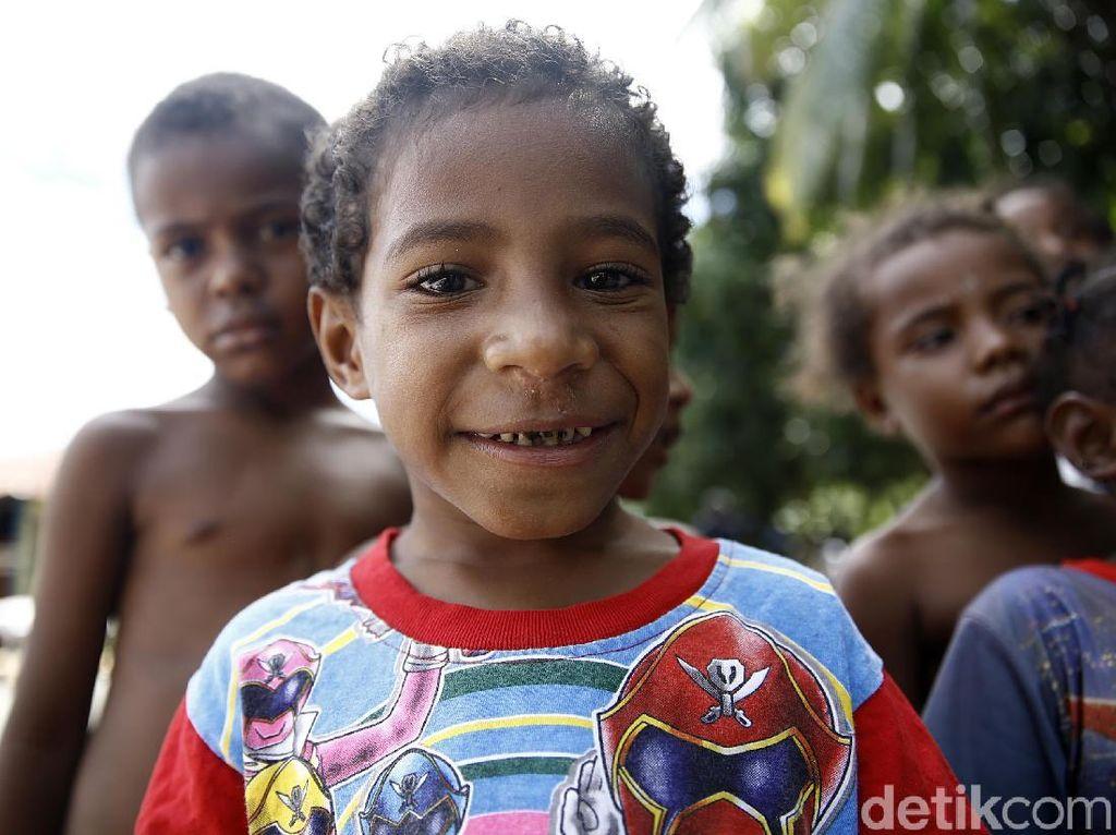 Seorang anak memamerkan senyum manisnya di depan kamera.